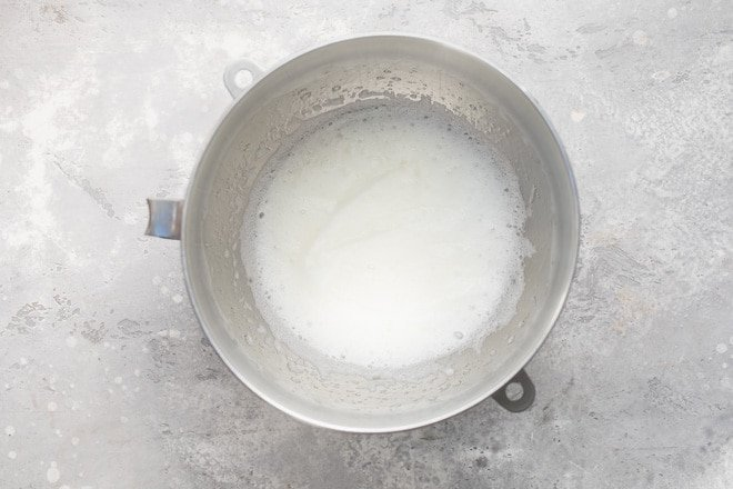 Egg whites whipped in a mixing bowl.