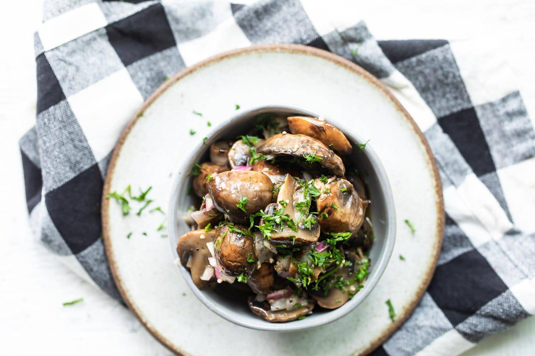 Marinated mushrooms in a gray bowl.