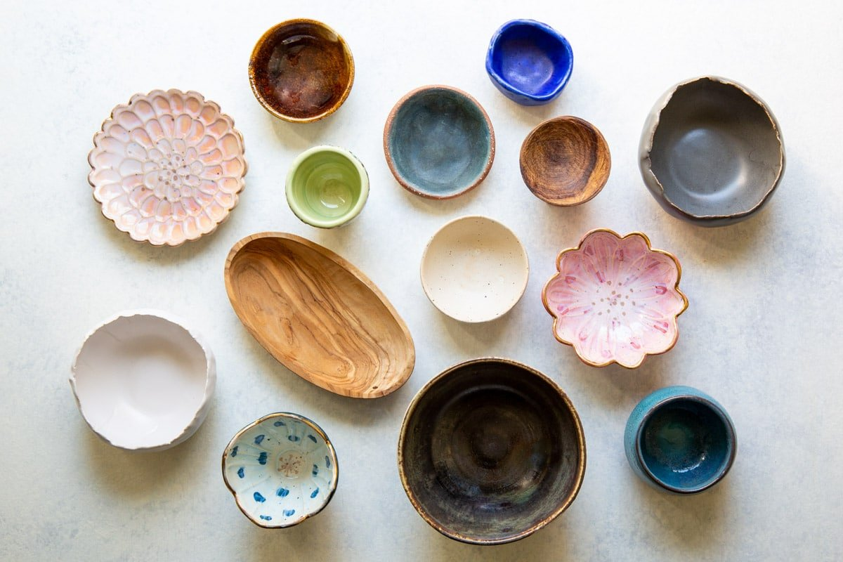 A collection of bowls and dishes for charcuterie display.