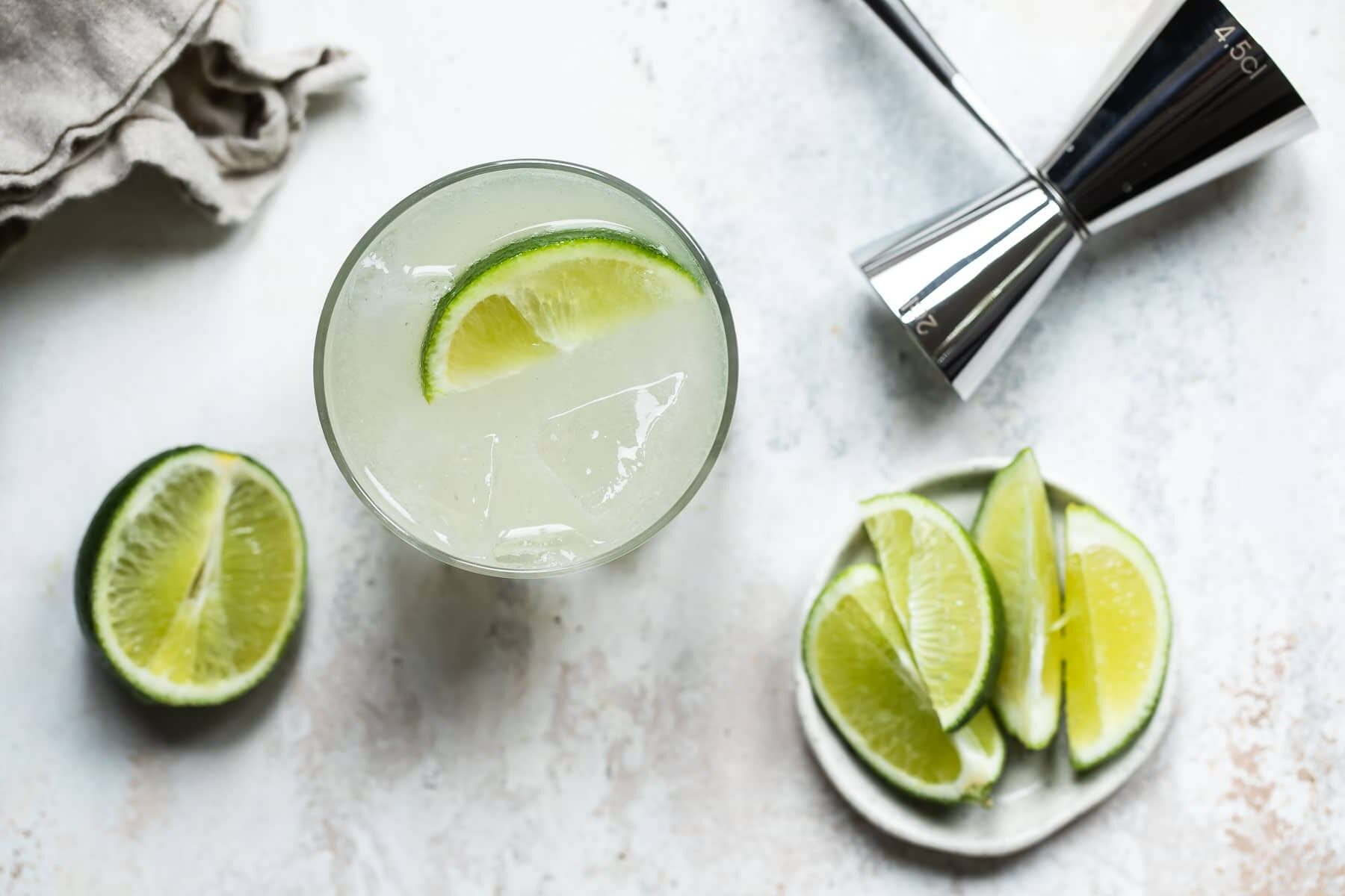 A Paloma cocktail in a rocks glass garnished with lime.