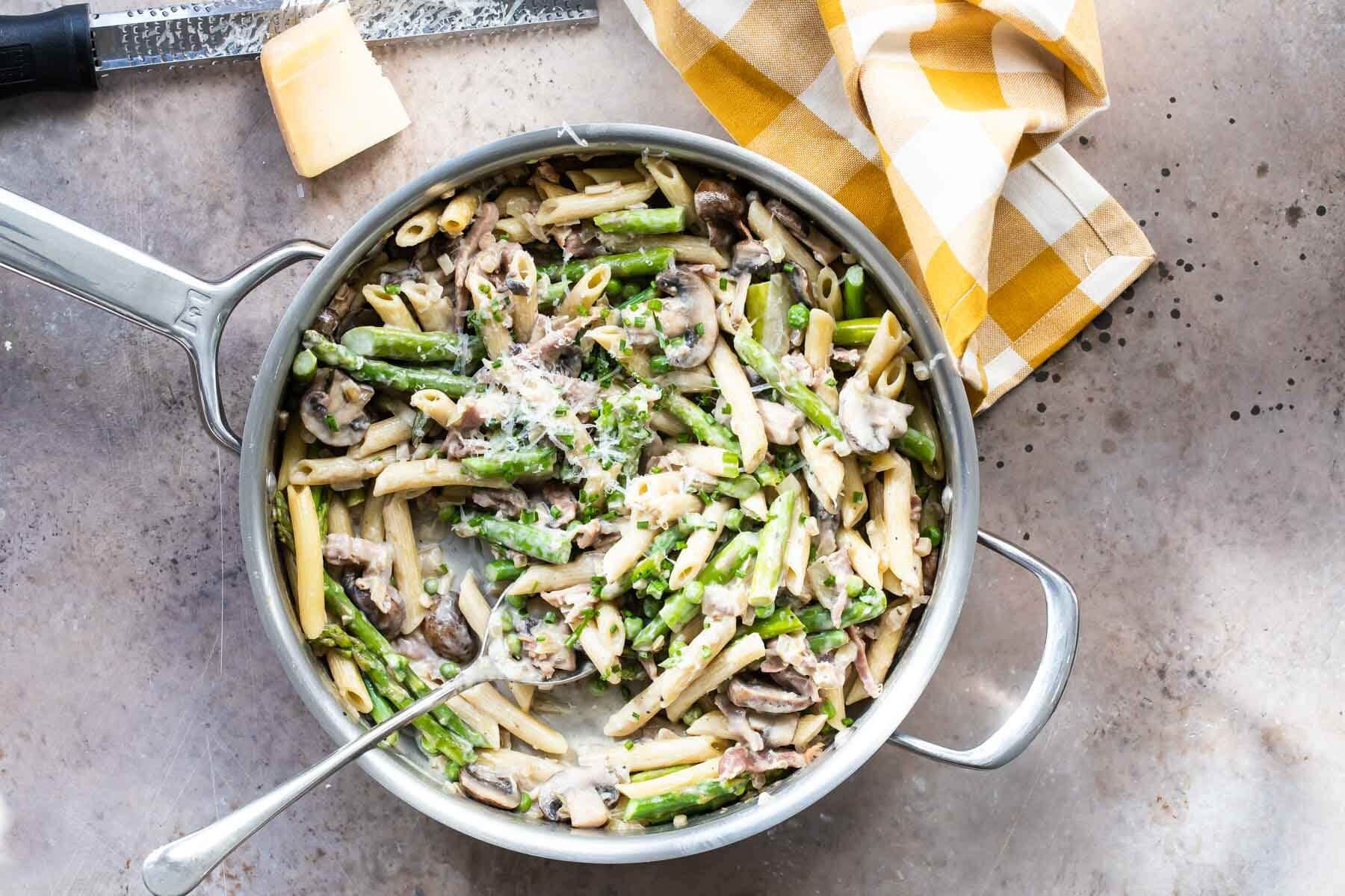 Pasta with peas and prosciutto in a silver skillet.
