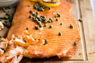 Smoked salmon on a wooden board with capers and lemon slices on top.