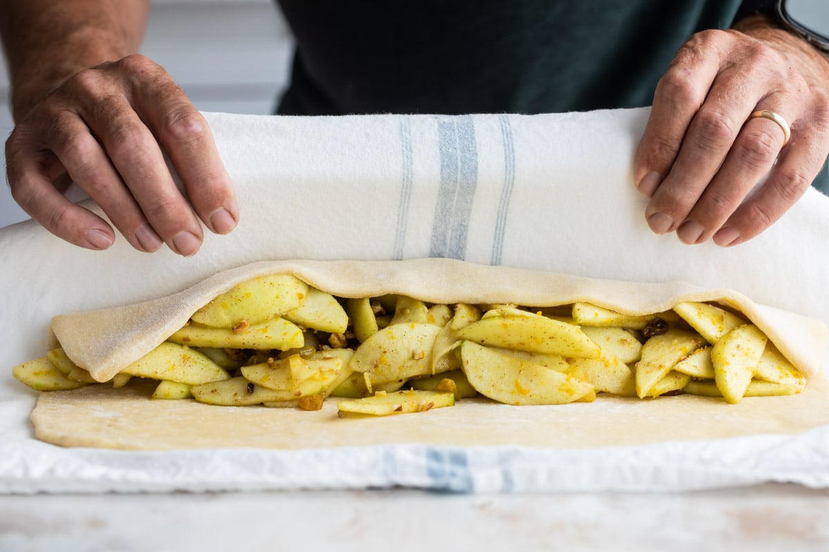 Filling an apple strudel and closing the dough.