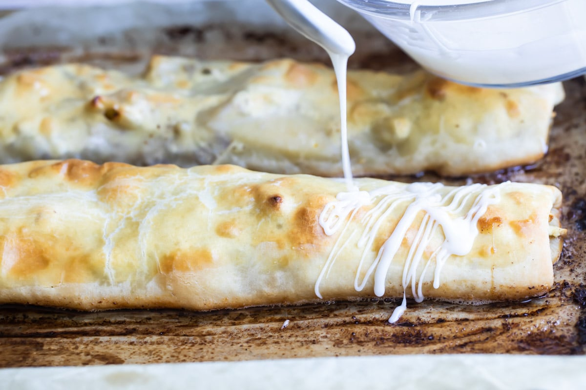 Two apple strudels on a baking sheet.