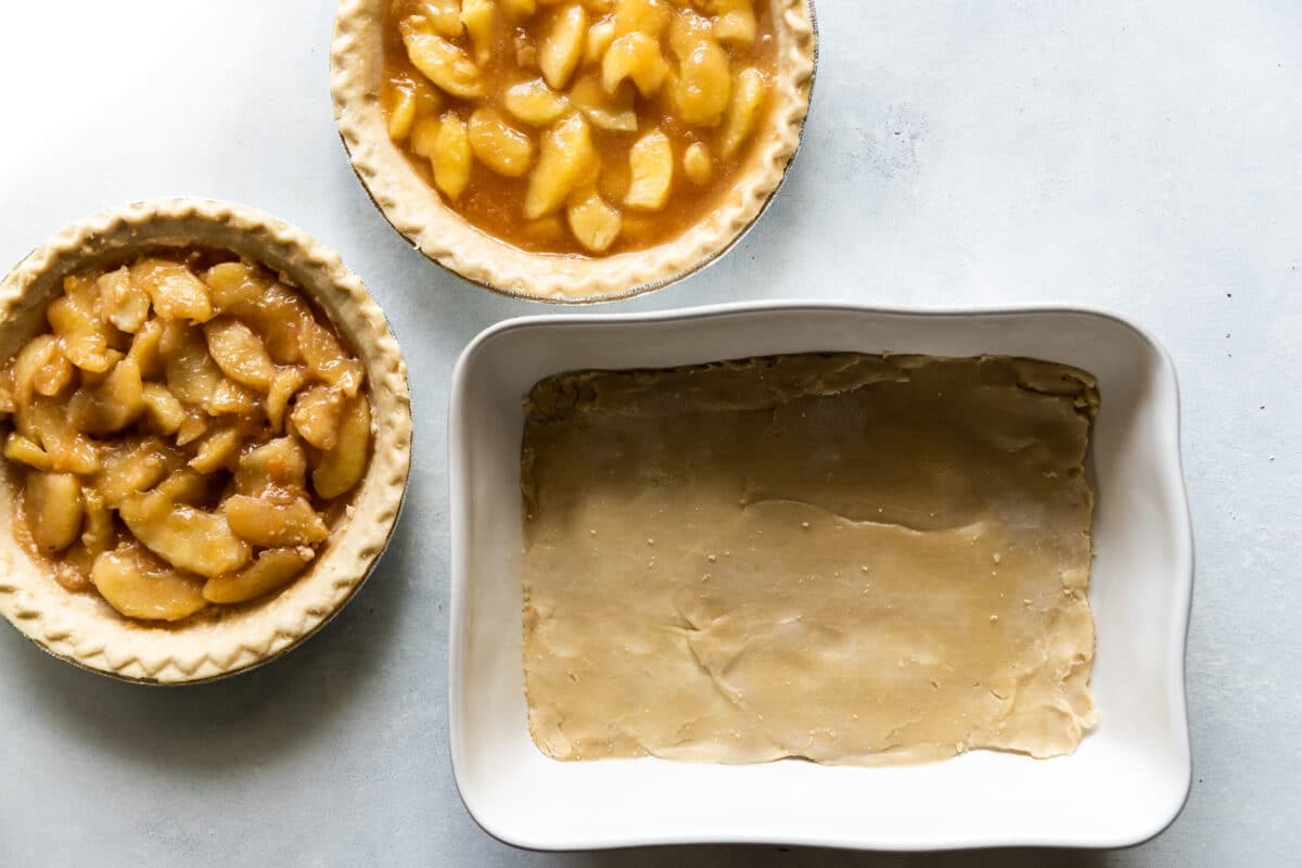 A baking dish with pie crust in the bottom and bowls of apple pie filling next to it.