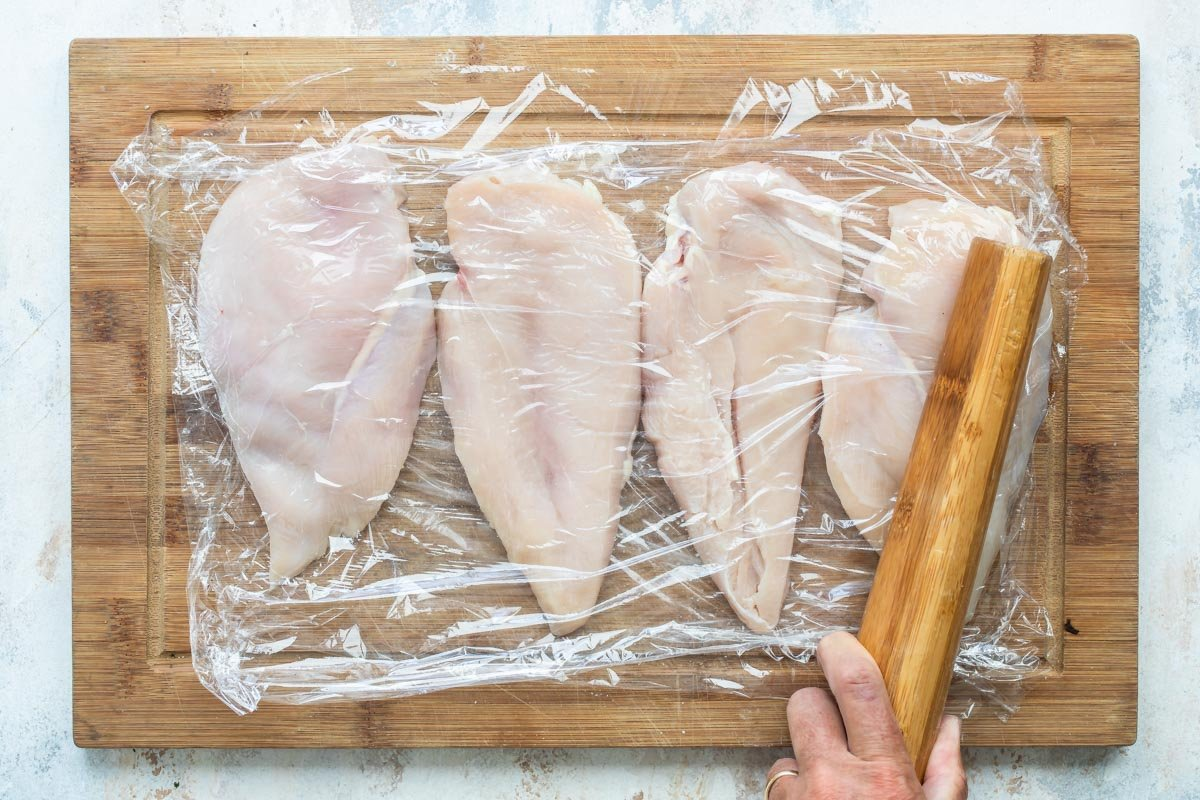 Pounding chicken cutlets thin under plastic wrap.