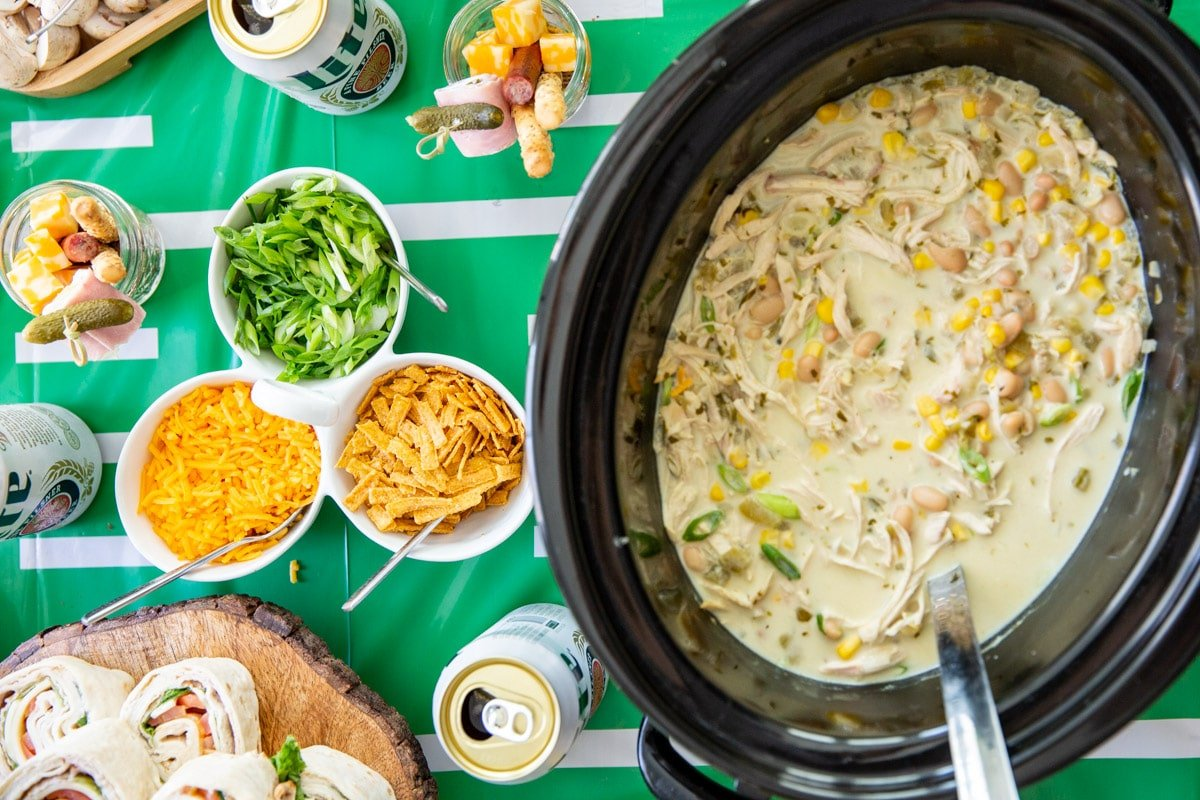 White chicken chili in a slow cooker with toppings nearby.