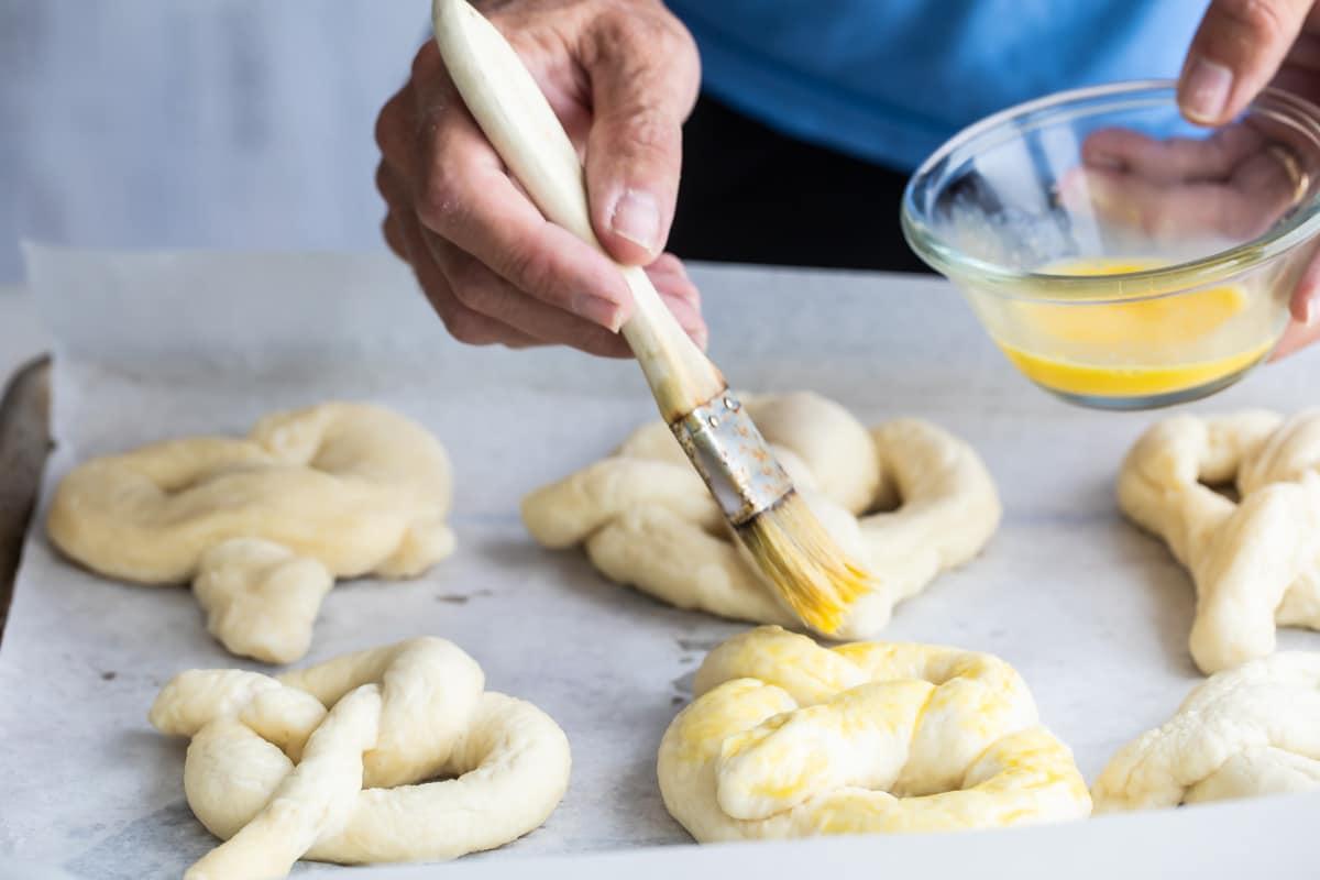 Brushing soft pretzels with egg wash.