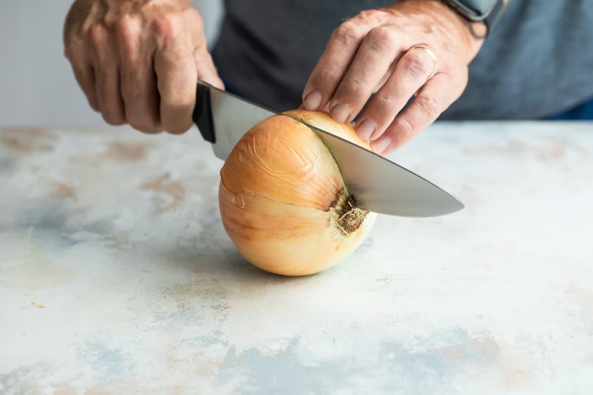 Cutting an onion in half.