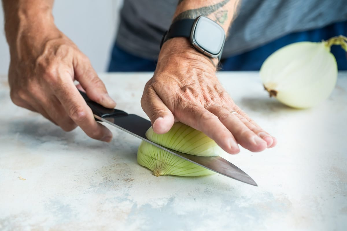 Making slices lengthwise through an onion for dicing.