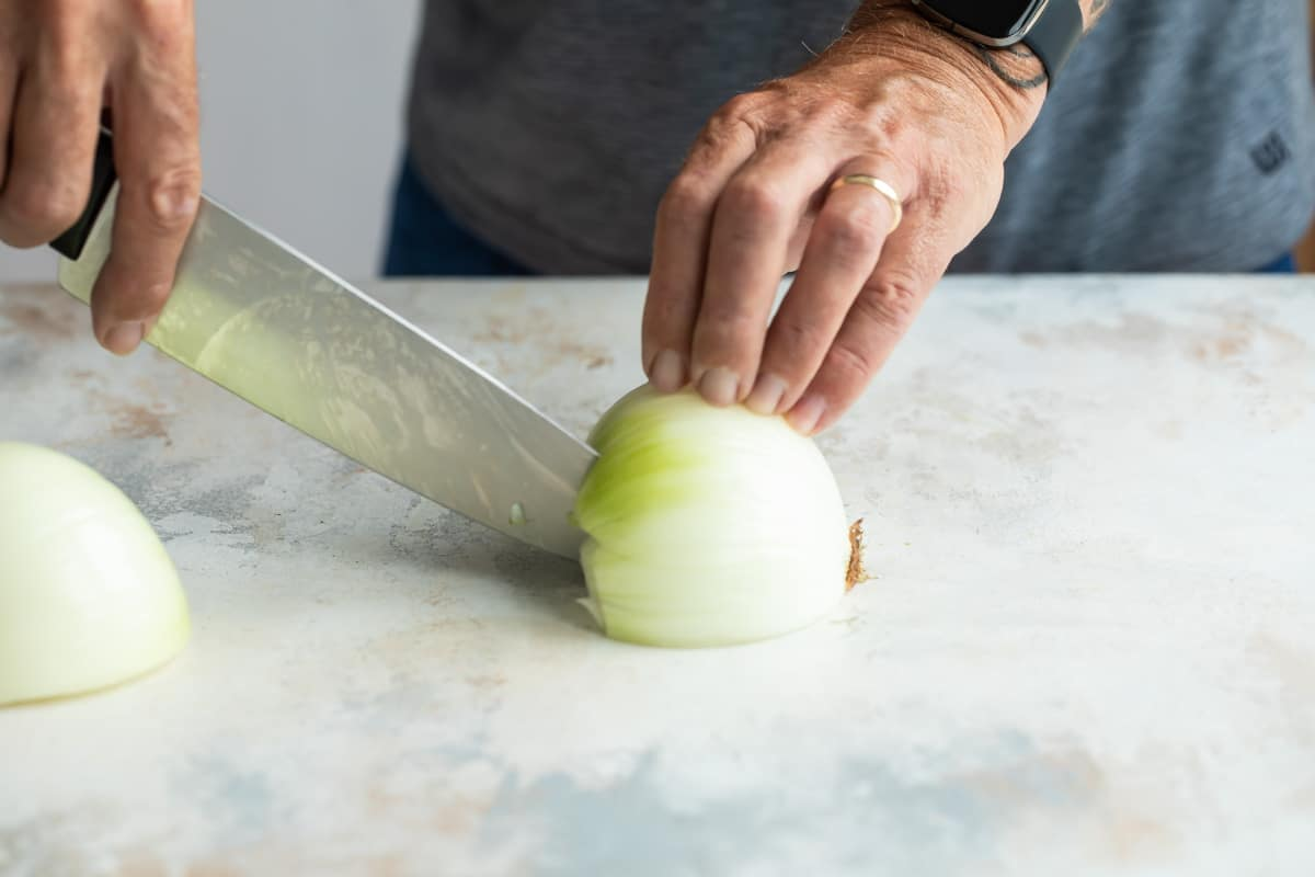 Making straight cuts down an onion to dice.