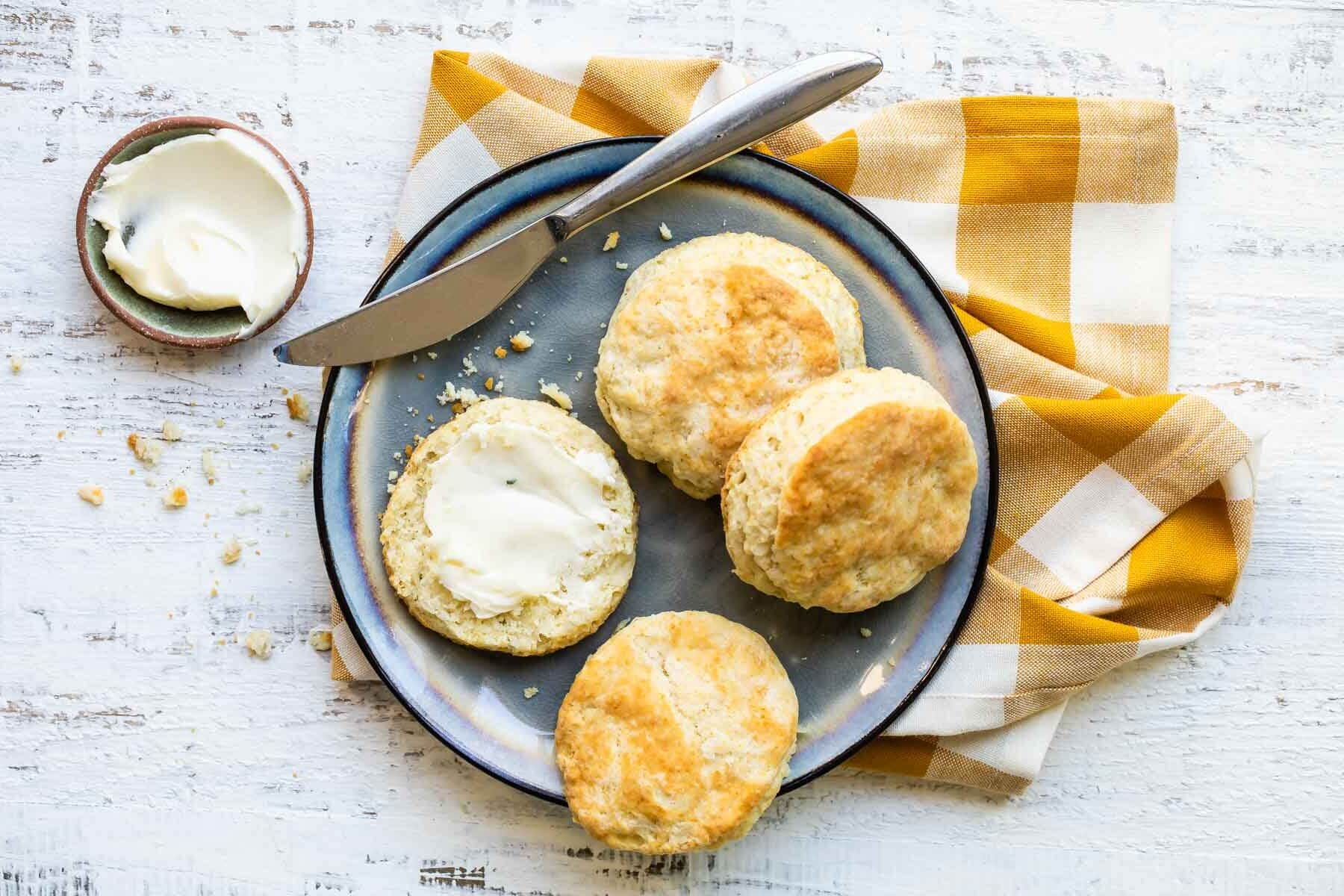 A plate with biscuits cut in half, one piece slathered in butter.