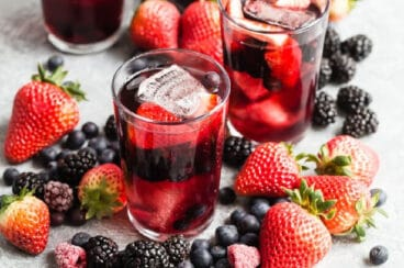 3 glasses and a pitcher of iced tea berry sangria surrounded by piles of fresh berries.
