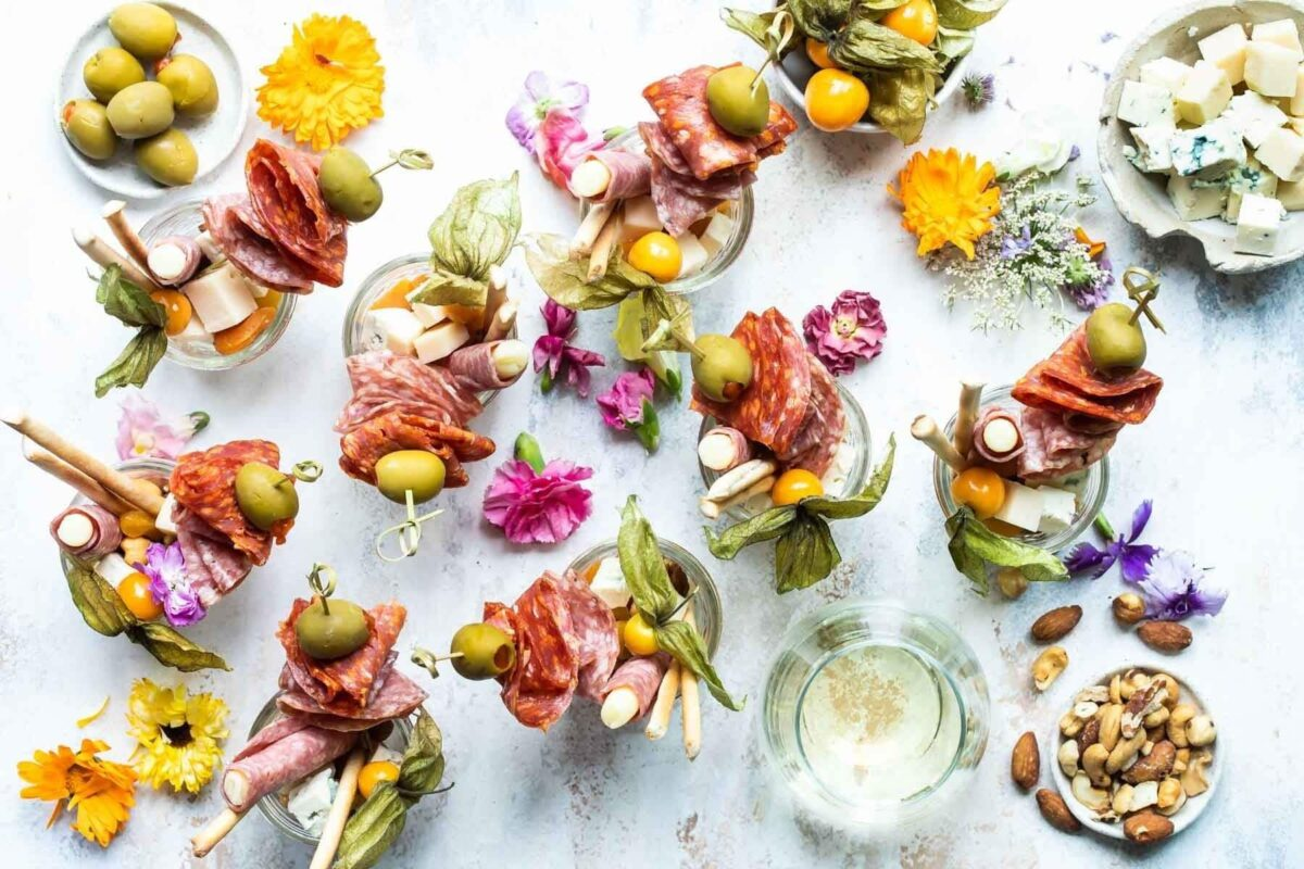 Jarcuterie, an individual portion of charcuterie assembled in a single-serving jar. Contains salmon, cheese, nuts, dried fruit, olives, and breadsticks.x