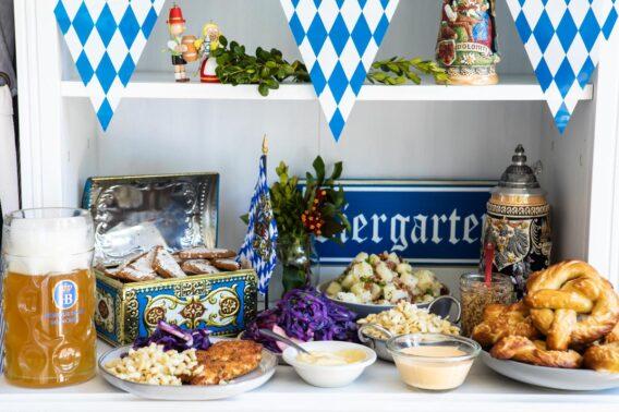 A table of Oktoberfest food including schnitzel, spaetzle, soft pretzels, German potato salad, Lebkuchen, and beer.
