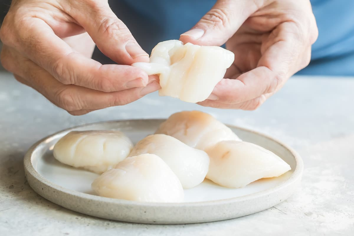 Removing the beard from a scallop.
