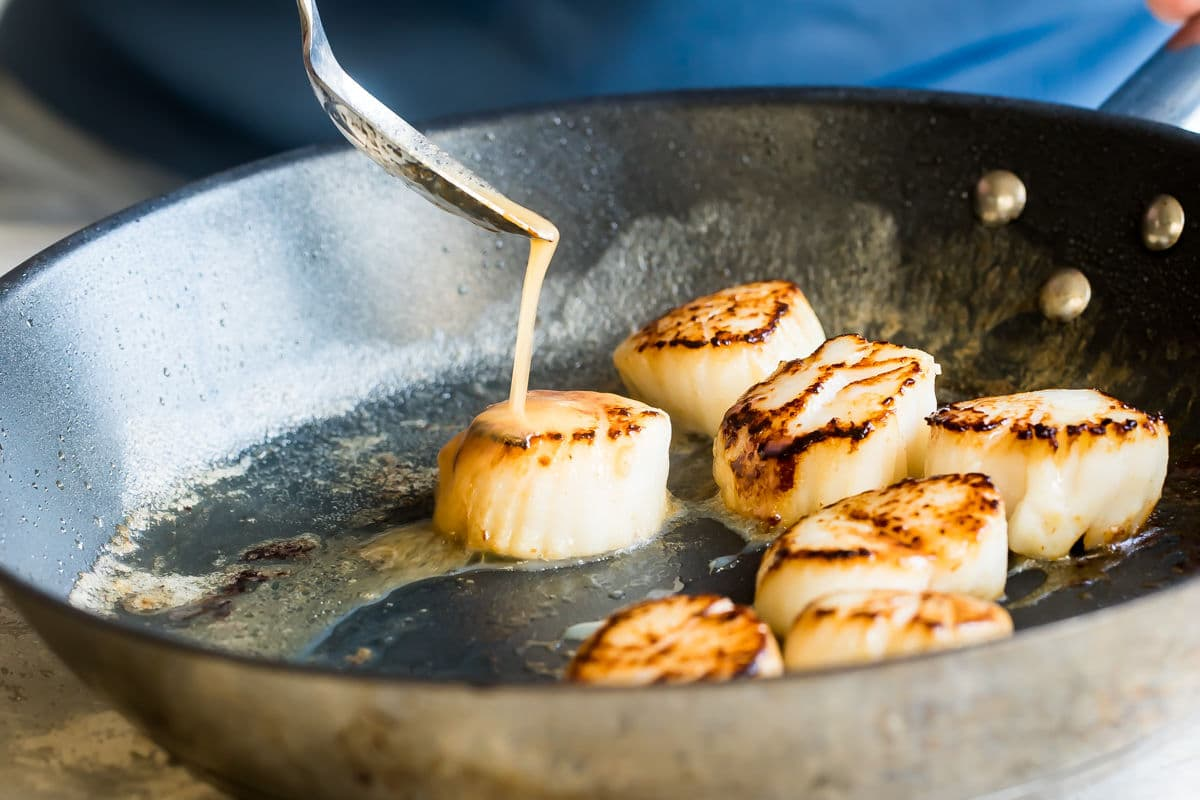 Lemon butter sauce being drizzled onto pan-seared scallops in a black pan.
