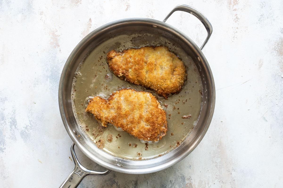 Pork schnitzel frying in a pan.