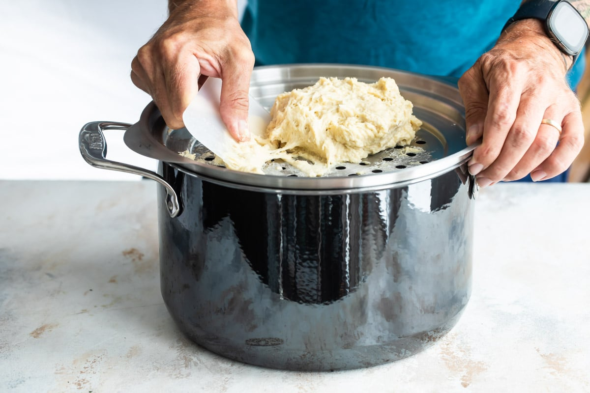 Pushing spaetzle dough through a metal lid with holes to make the dumplings.
