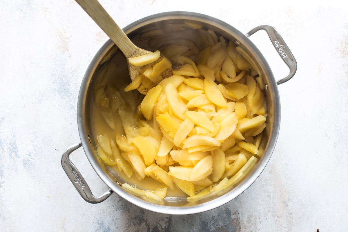 Apples being cooked in a stockpot.