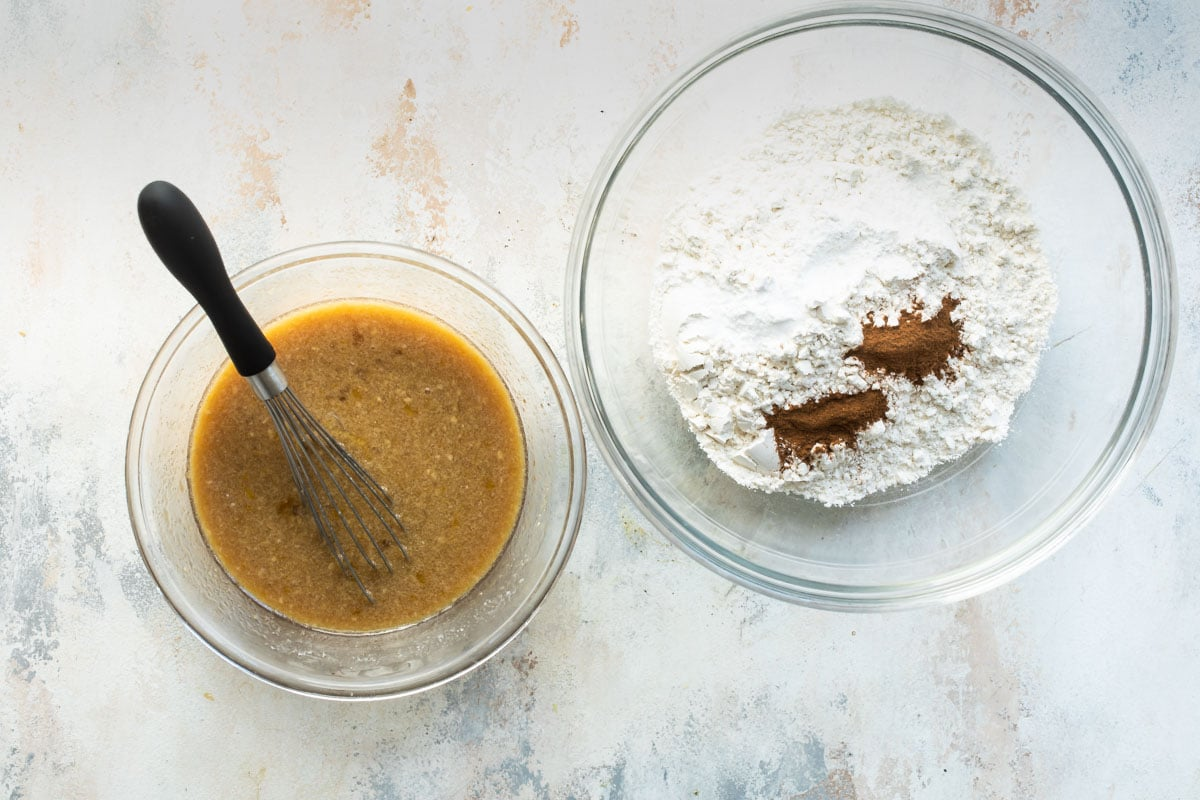 A brown liquid mixture in a clear bowl next to a clear bowl of dry ingredients.