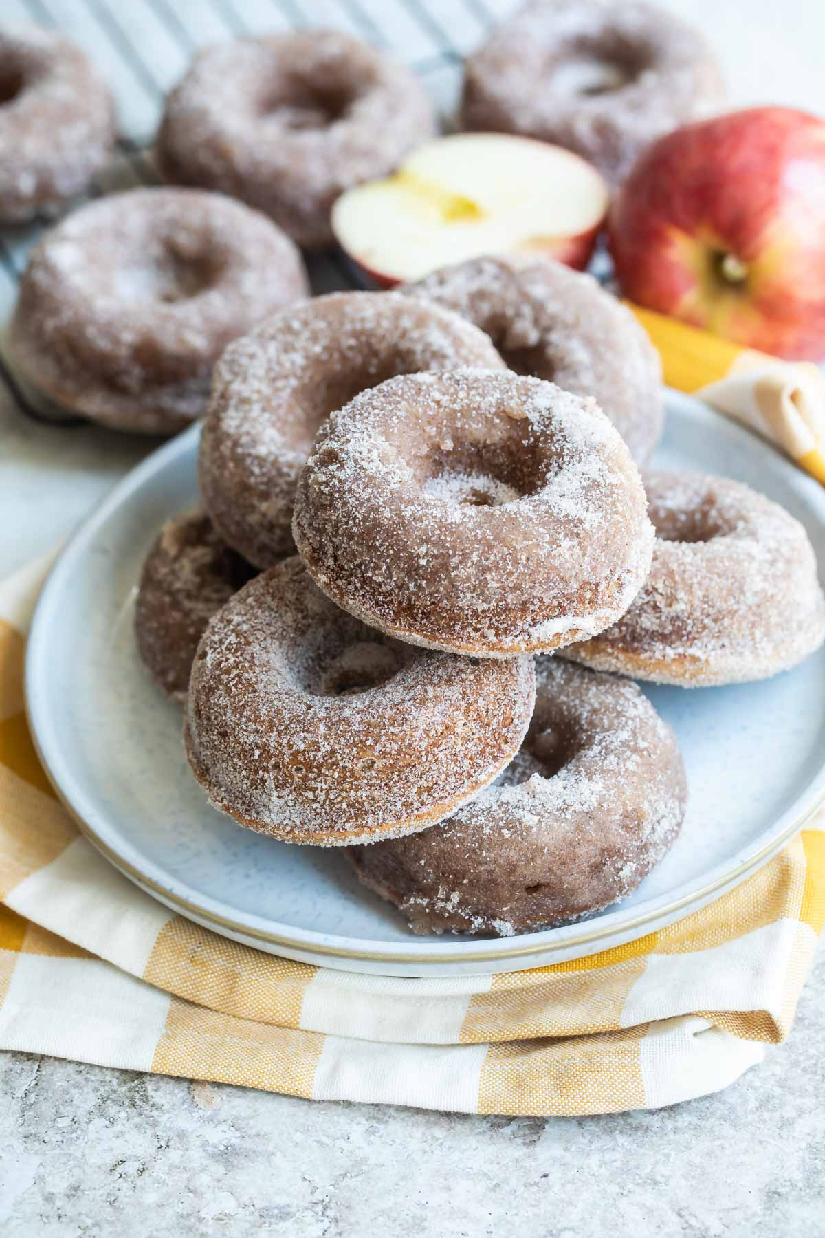 Seven apple cider donuts on a gray round plate.