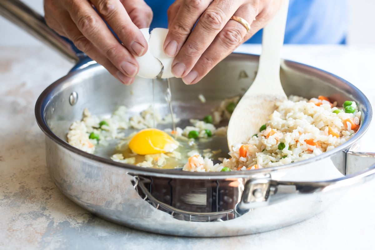 Someone cracking an egg into a fried brown rice mixture.