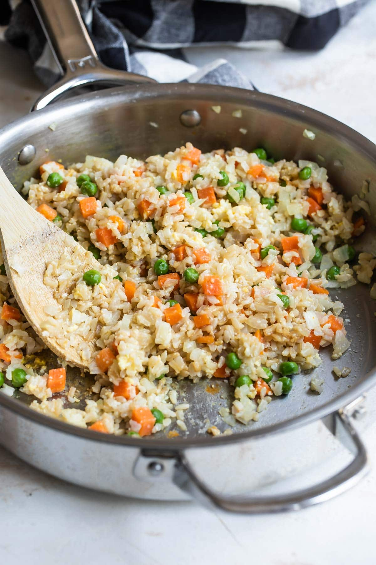 Brown fried rice in a silver skillet.