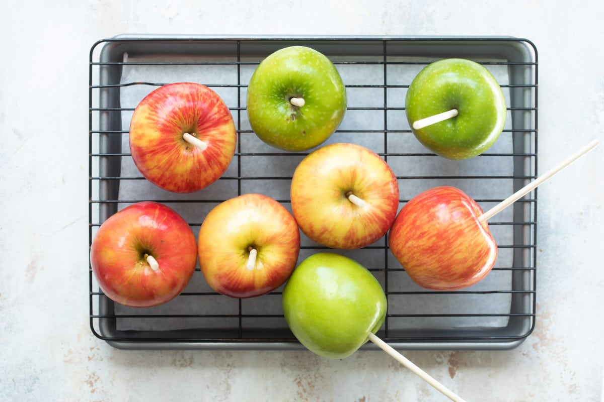 Eight apples with wooden skewers in them resting on a cooling rack.