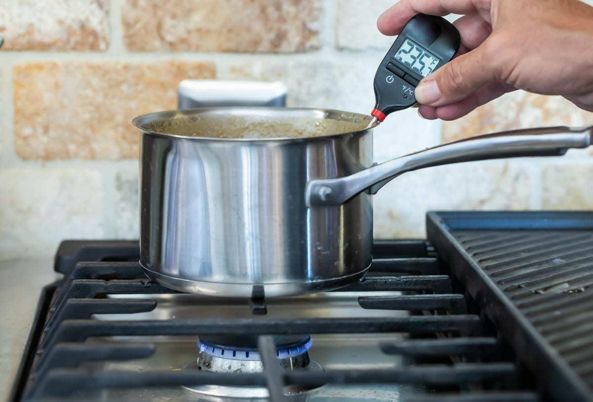 Someone temping caramel in a silver pot over a stove burner.