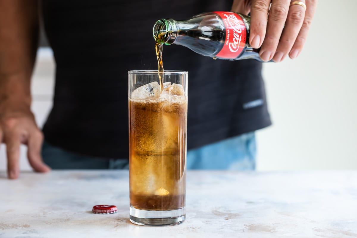 Adding coca cola to a Charro negro cocktail.