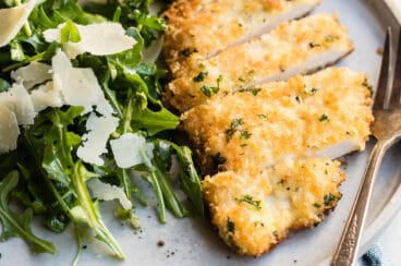 Chicken Milanese on a gray plate with a side of greens.