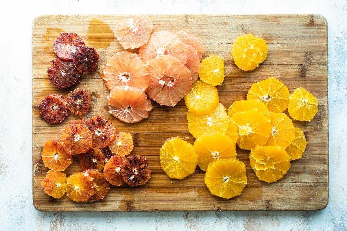Citrus fruit cut up on a wooden cutting board.