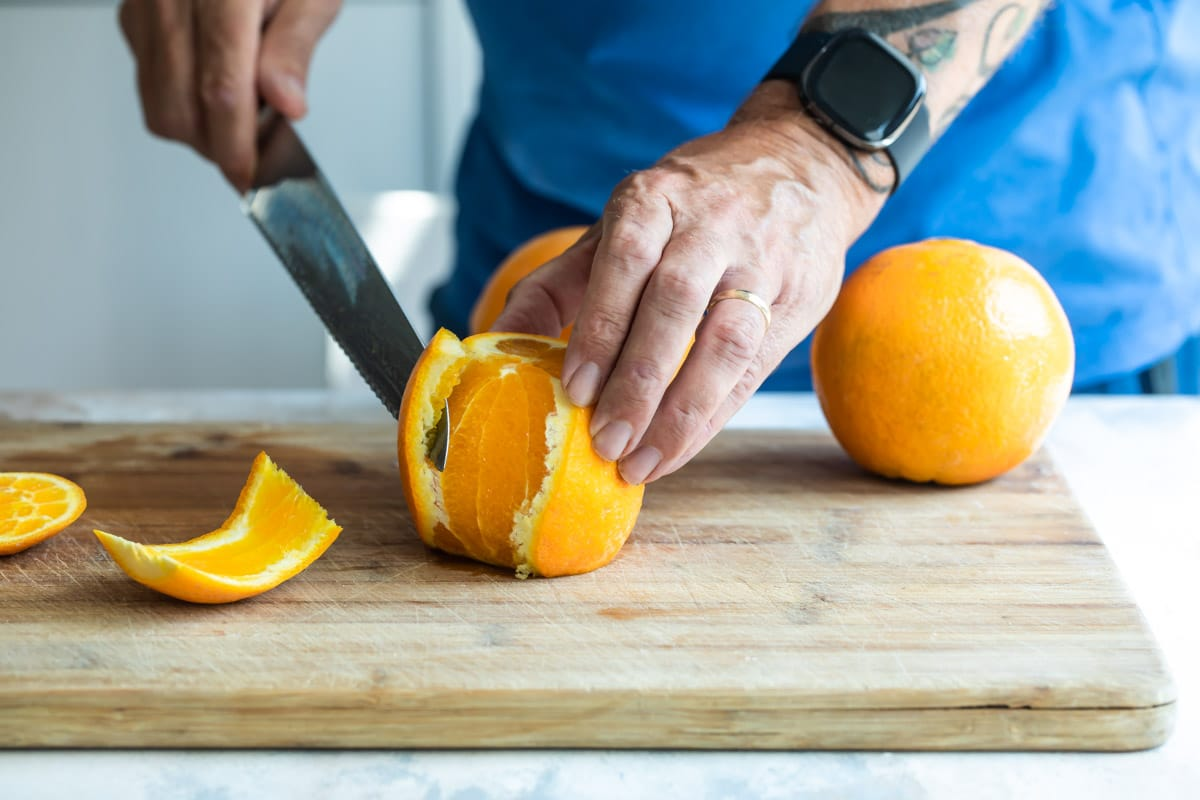 Someone cutting the peel off of an orange.
