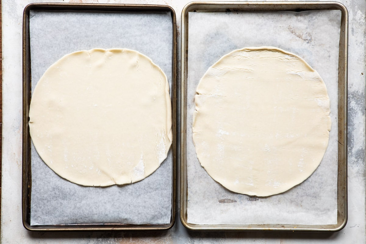 Dough on two cookie sheets for cranberry cheesecake galette.