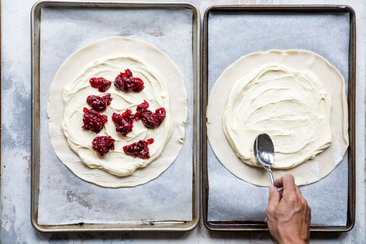 Two cookie sheets with cranberry cheesecake galettes being made.