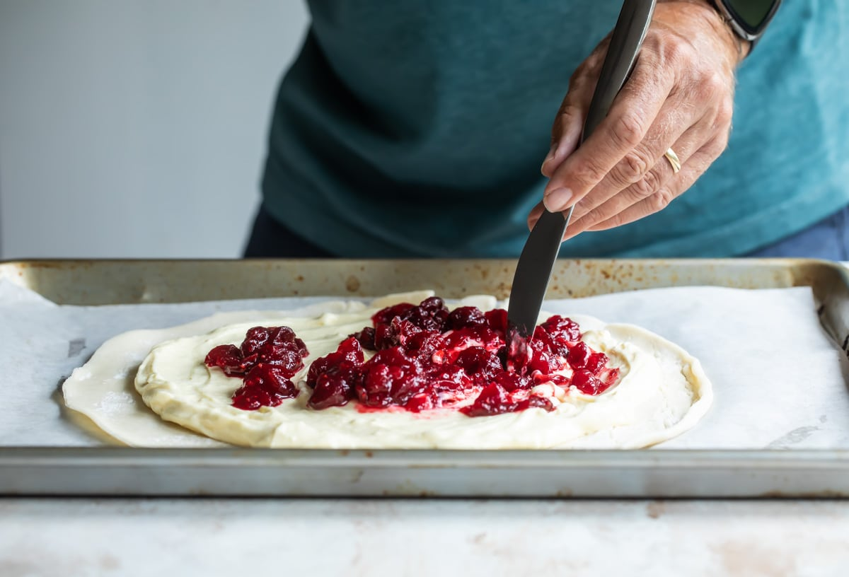 Someone spreading cranberries on dough to make a cranberry cheesecake galette.