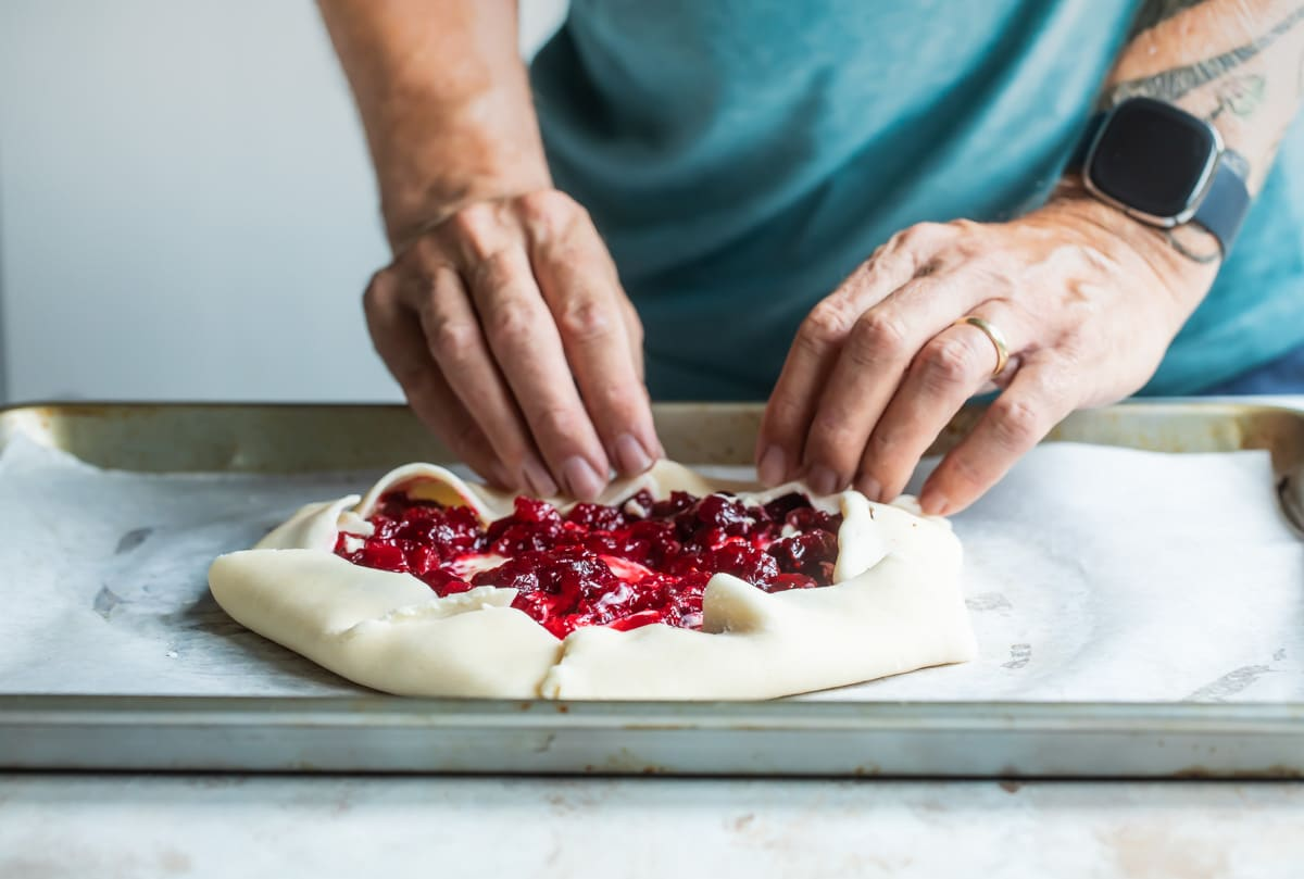 Someone folding an uncooked cranberry cheesecake galette on a piece of parchment paper on a baking sheet.