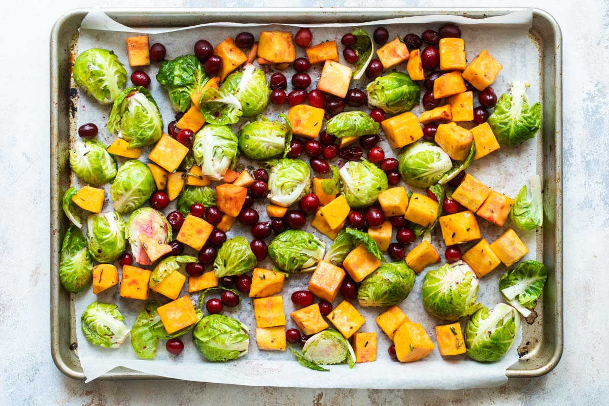 Uncooked harvest roasted vegetables on a parchment paper lined sheet pan.