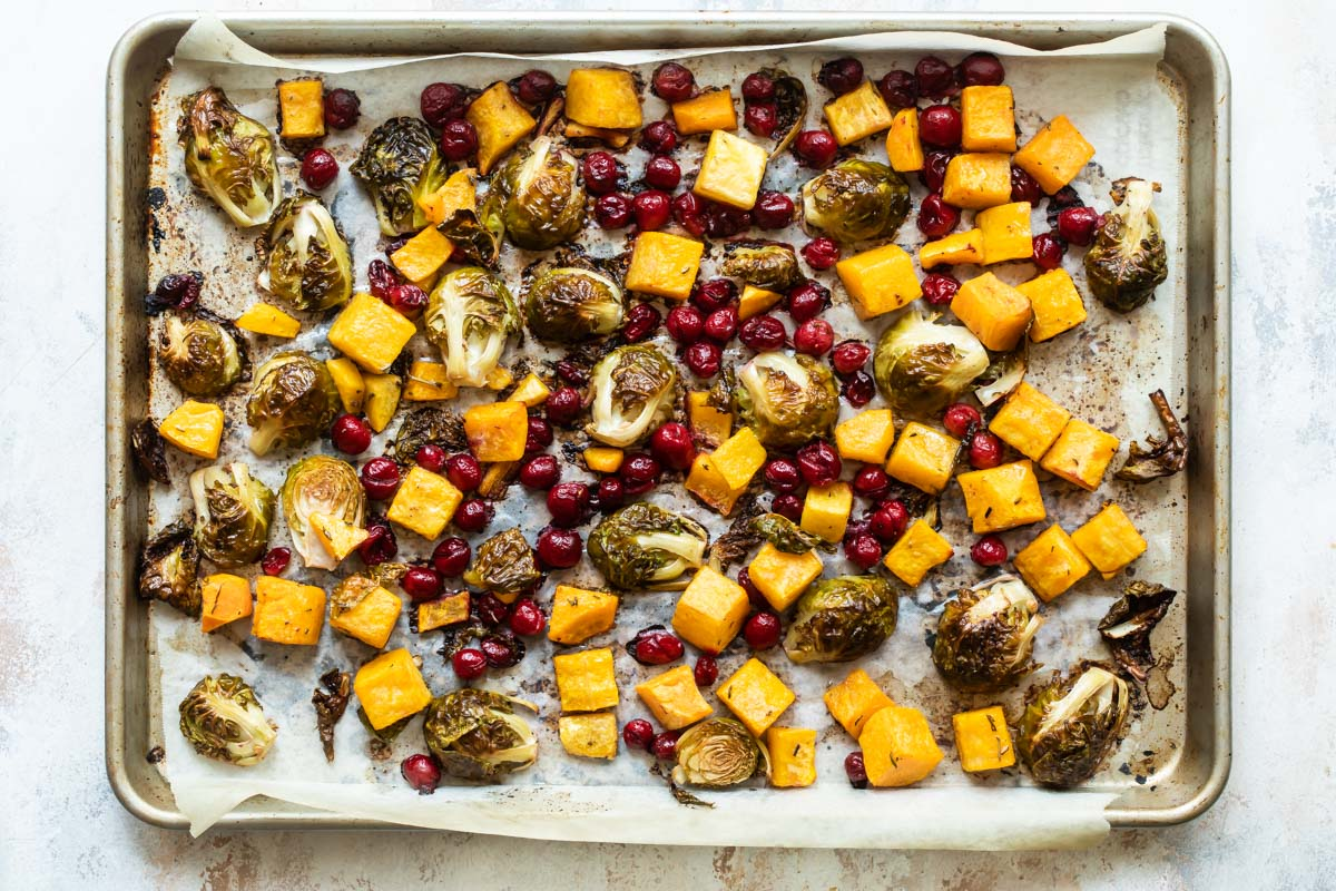 Harvest roasted vegetables on a parchment paper lined sheet pan.