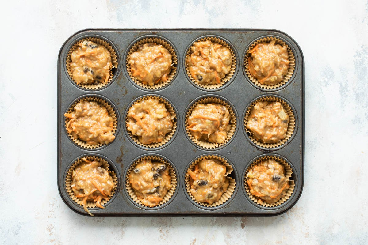 Twelve unbaked morning glory muffins in a muffin tin.