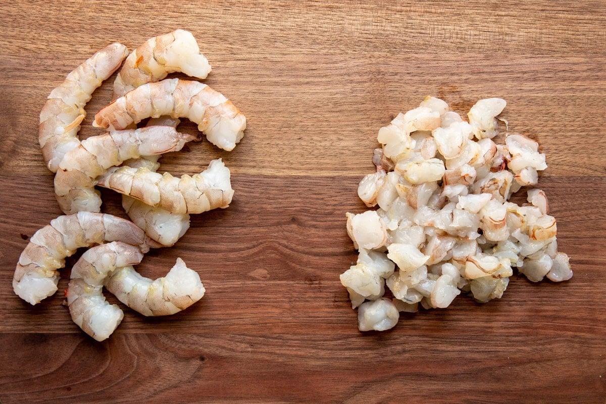 Raw shrimp on a cutting board.