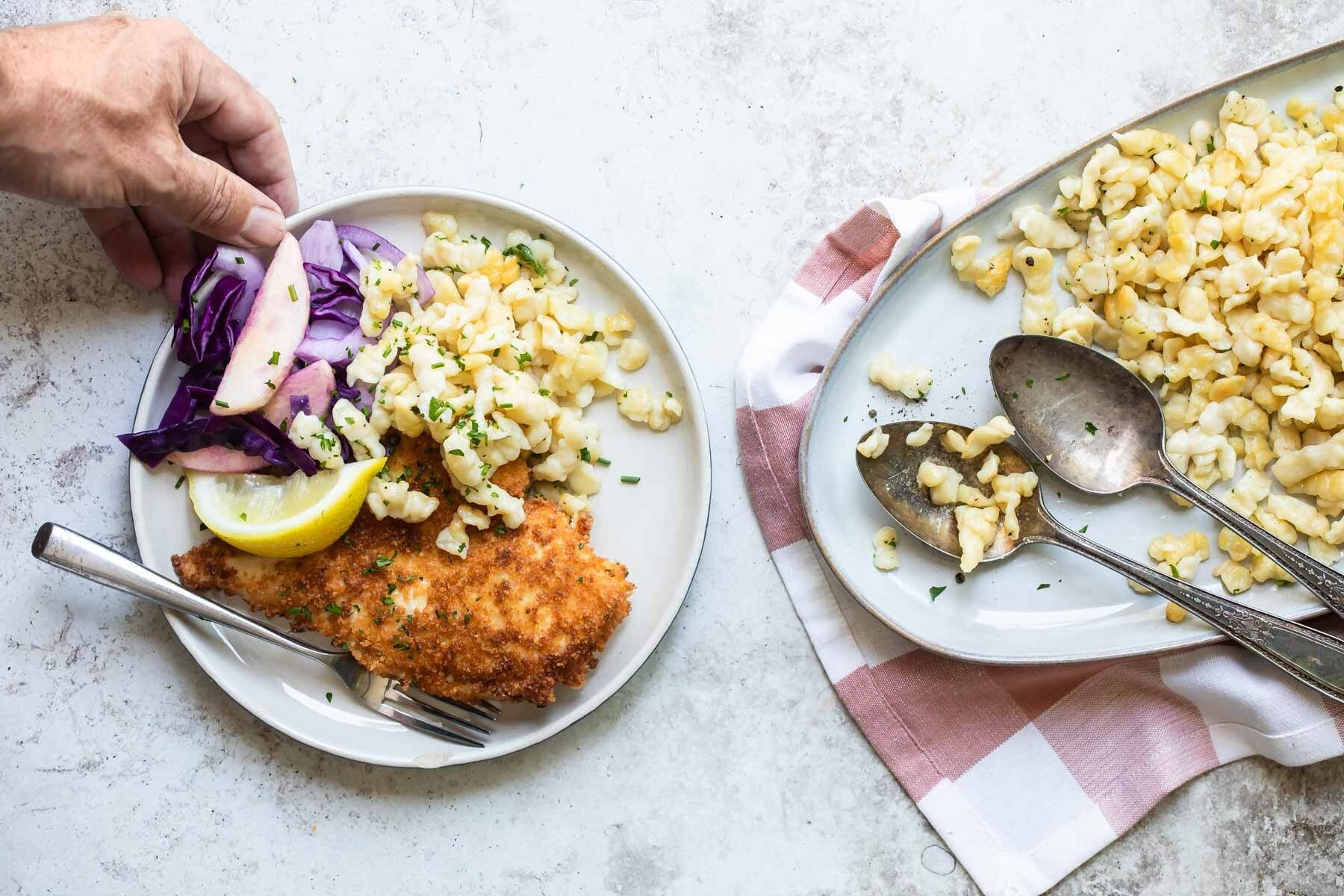 Plates with spaetzle, schnitzel, and red cabbage.