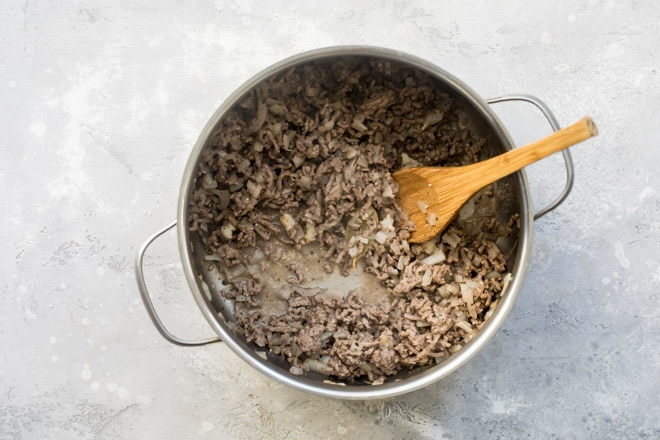 Browned meat and onion in a saucepan.