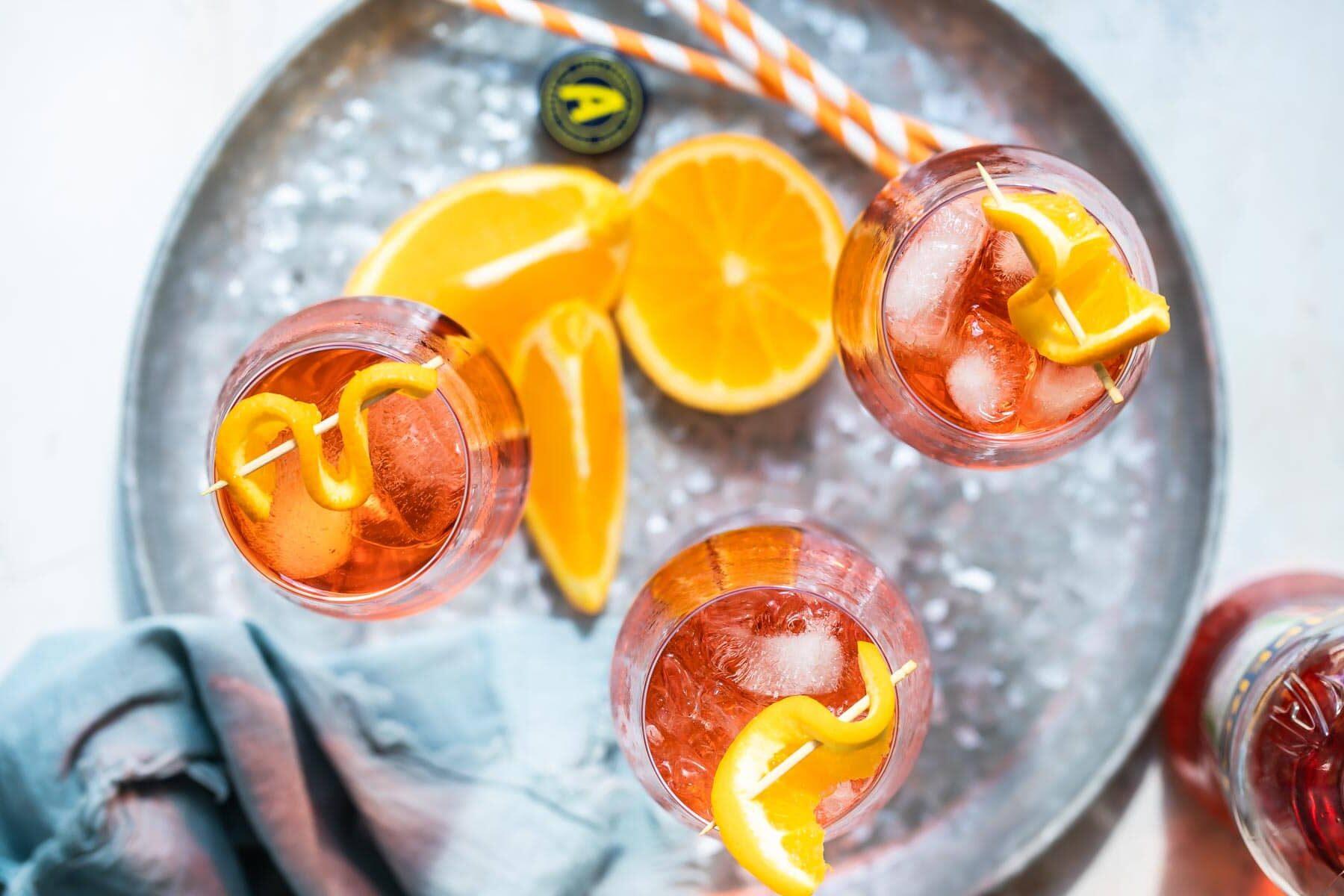 3 Aperol Spritz cocktails ona. metal tray.