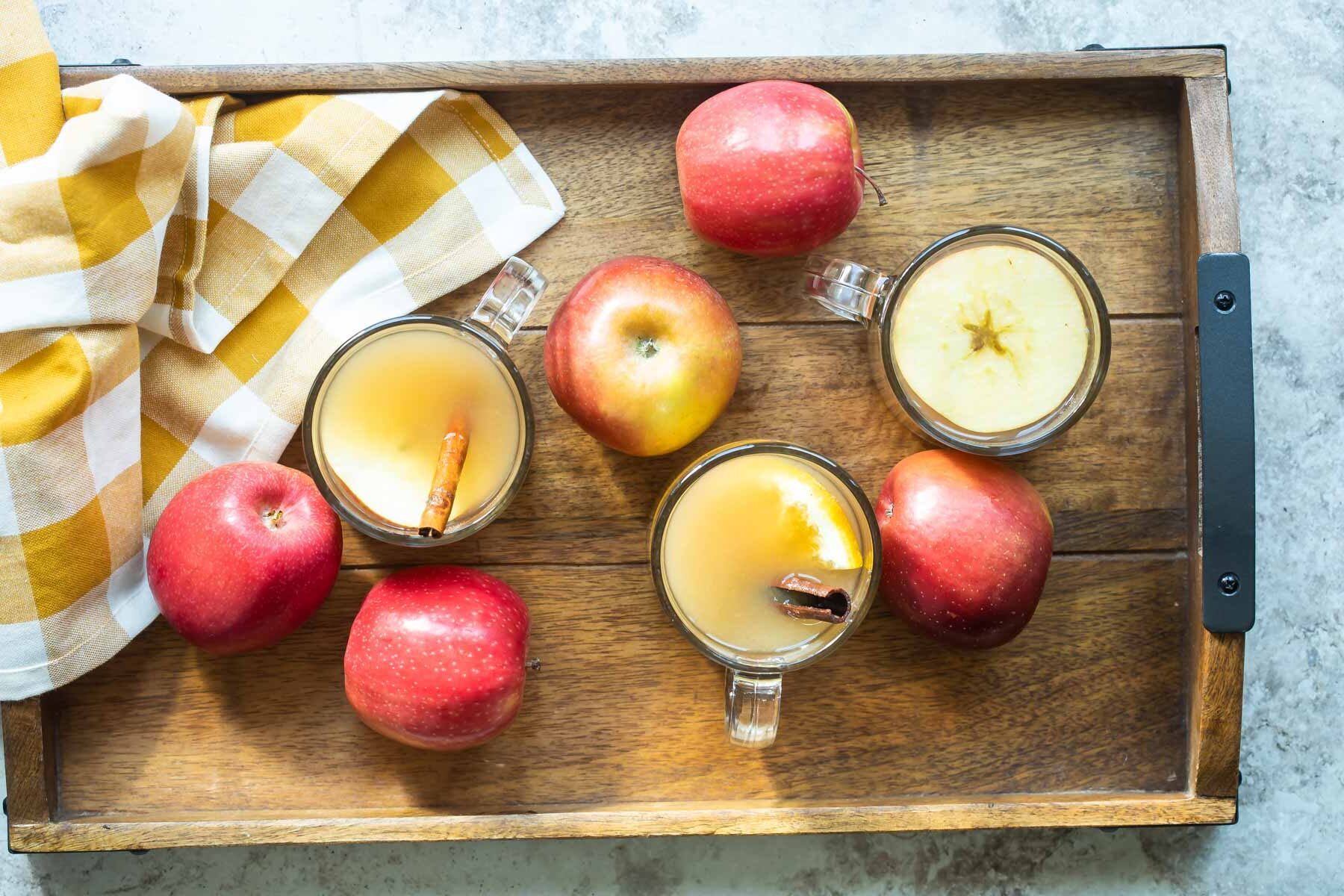 Apple cider in a clear glasses on a wooden serving tray.