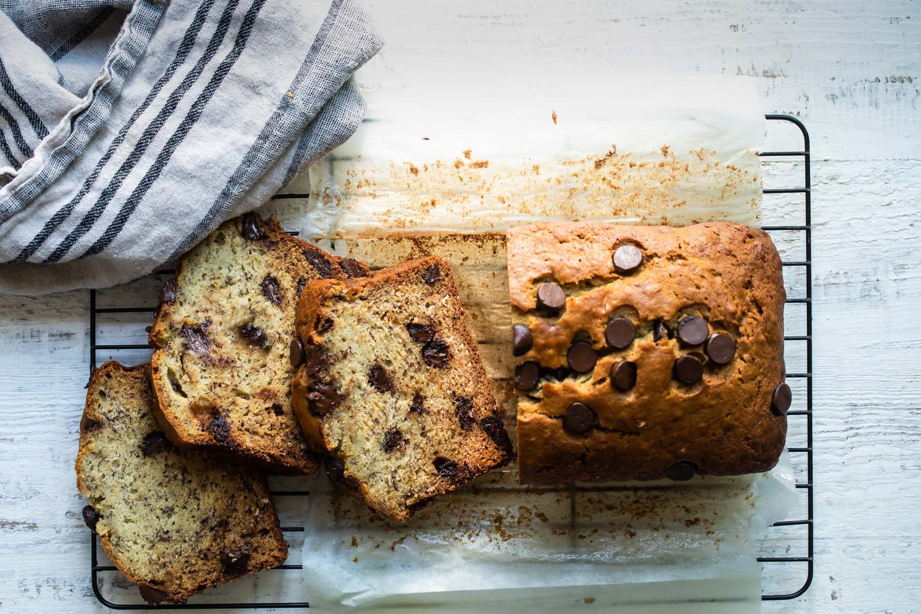 A loaf of banana bread with three pieces sliced on a cooling rack.