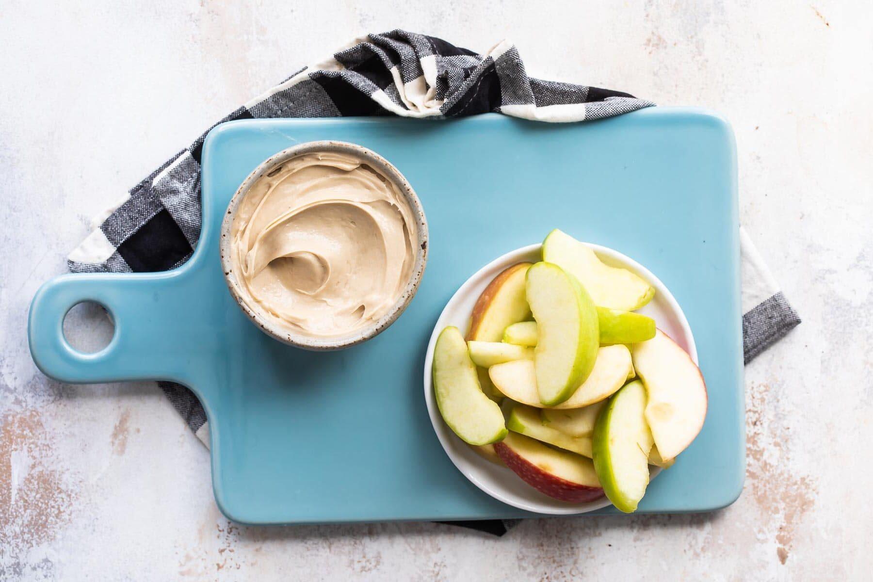 Caramel apple dip and apples on a teal platter.