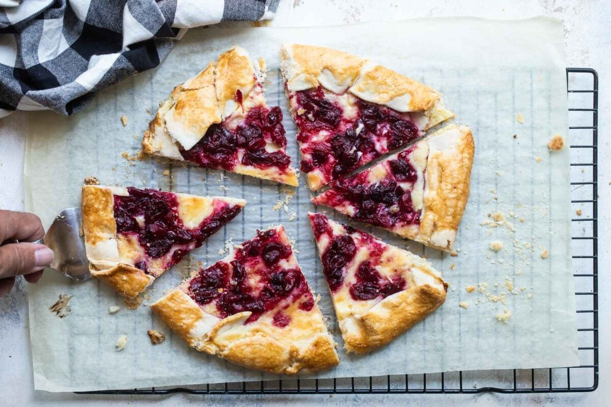 Cranberry cheesecake galette on a piece of parchment paper over a cooling rack.