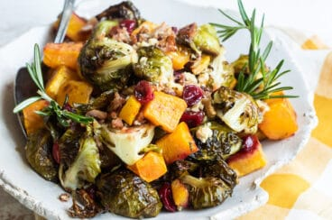 A serving of harvest roasted vegetables on a white plate.